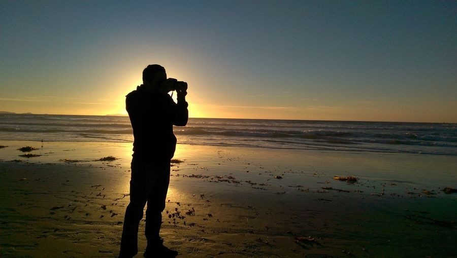 Full Length Of Rear View Silhouette Man Photographing Sea Against Sky At Beach