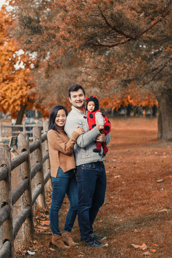 Portrait of parents with cute daughter in park during autumn