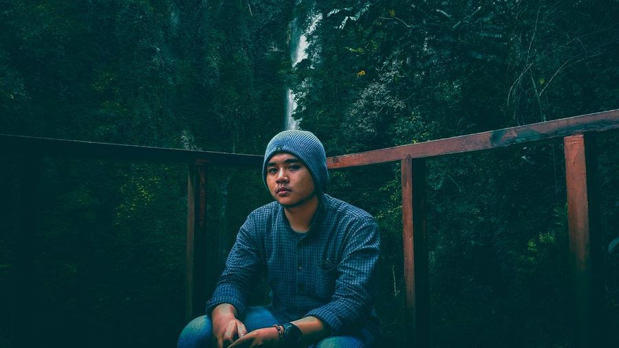 Young man looking away while sitting on railing in forest