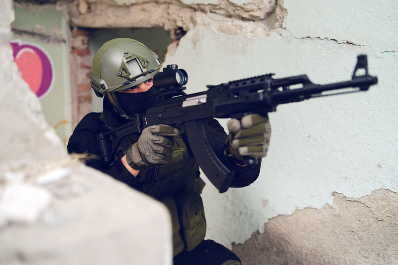 Army soldier aiming gun in building