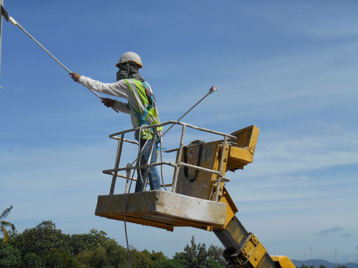 Low angle view of man standing on cherry picker against sky