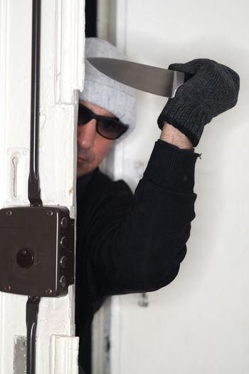 Thief with knife opening door