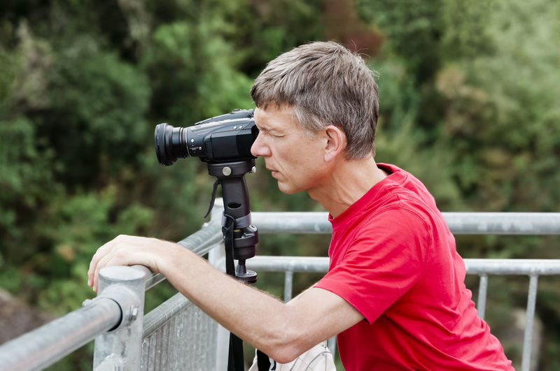Side view of man photographing on railing