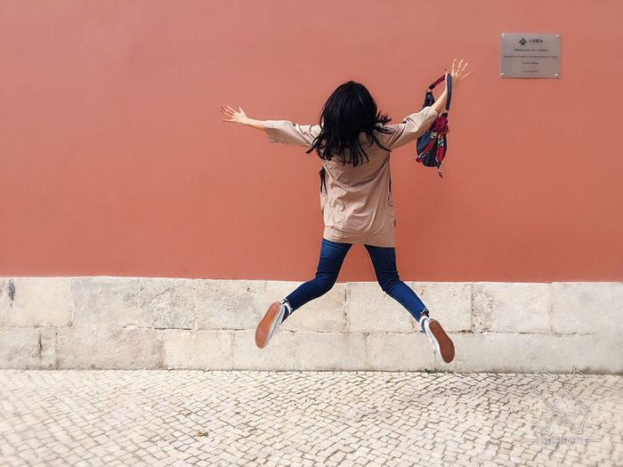 Rear view of excited woman jumping against coral wall