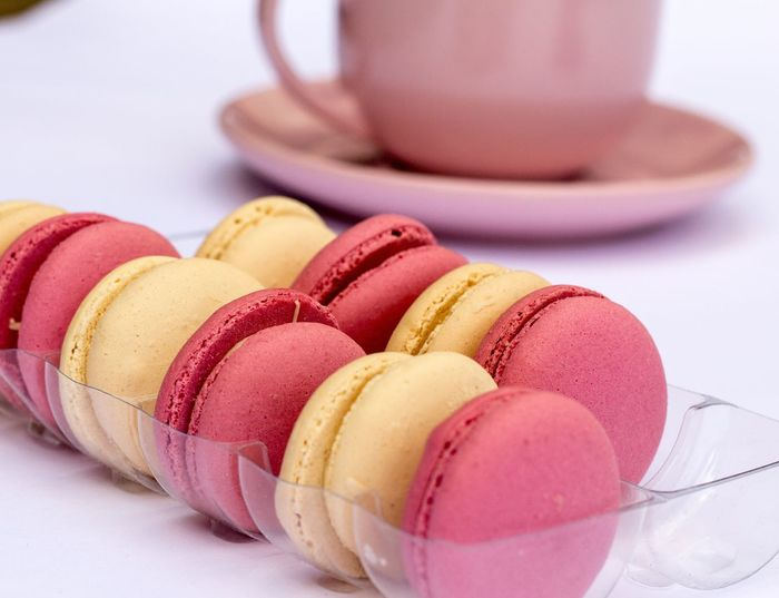 Close-up of macaroons in plastic container by cup on table