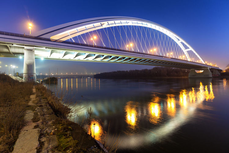Illuminated bridge over river against sky at night
