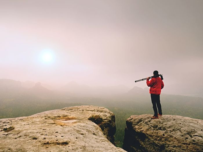 Photographer think about picture on peak in the misty mountains. landscape view of man