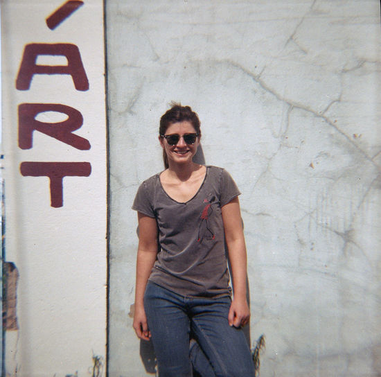 Analog portrait of a young woman against a concrete wall.