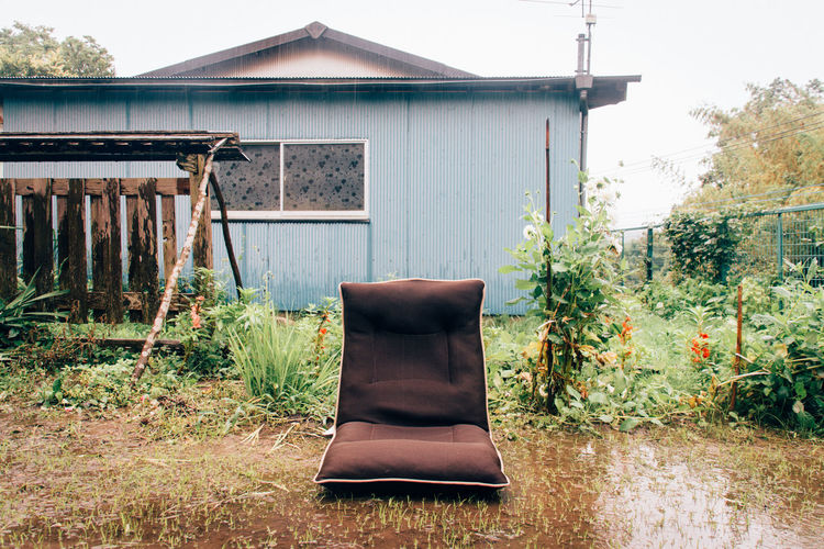 Empty seat in wet yard by house against clear sky