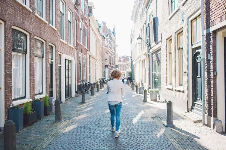 Rear view of woman walking on street amidst buildings