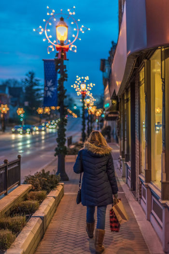 Rear view of woman walking on illuminated street at night