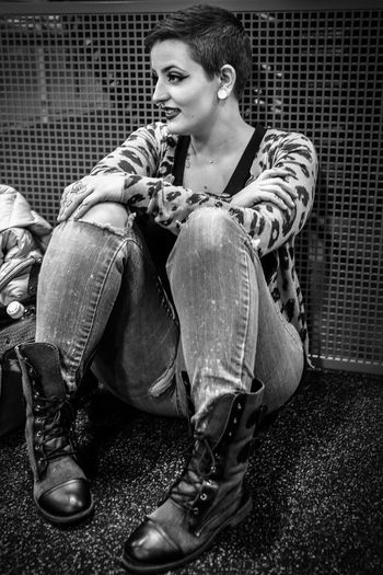 Woman Sitting By Metal Grate