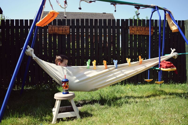 Hammock Day Nature Playground Childhood One Person Boys Sunlight Grass Males  Child Real People Leisure Activity Lifestyles Sunny Hanging Swing Outdoor Play Equipment Outdoors The Portraitist - 2018 EyeEm Awards The Still Life Photographer - 2018 EyeEm Awards Rope Swing Seesaw