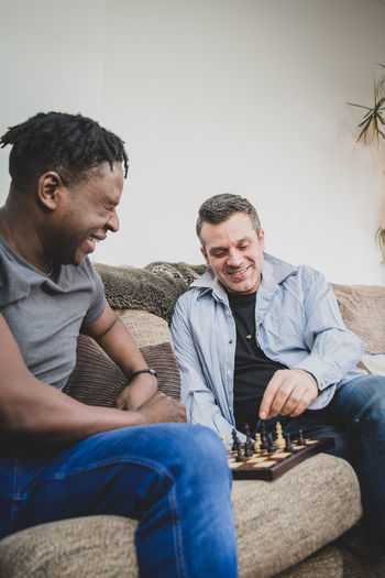 A gay couple enjoying time indoors at home, playing chess. Men Casual Clothing Couple Gay Lgbtq Mixed Race Chess Couch Husband Boyfriend Date Living Room Young Adult Love Gay Couple Black Ethnicit Handsome Sitting