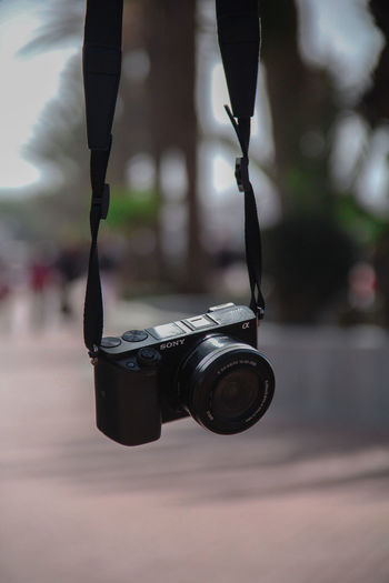 Low section of camera against blurred background