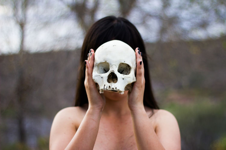 Topless Woman Holding Human Skull