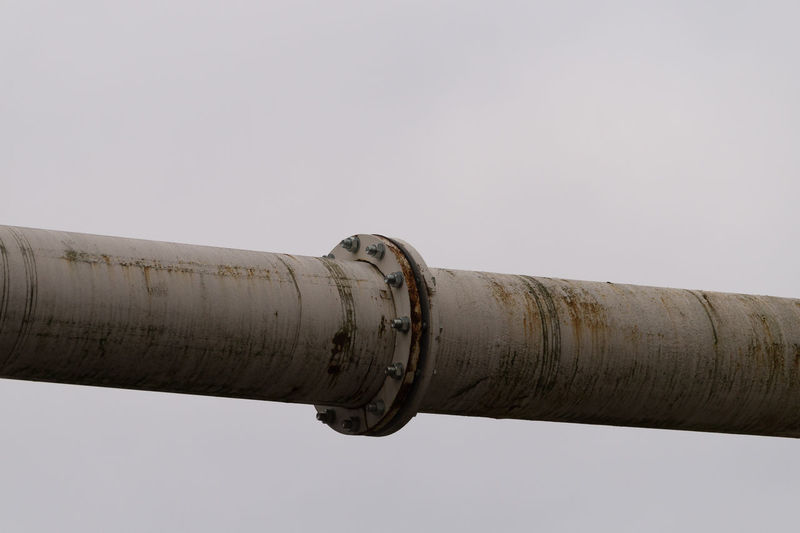 Low Angle View Of Metallic Pipeline Against Clear Sky