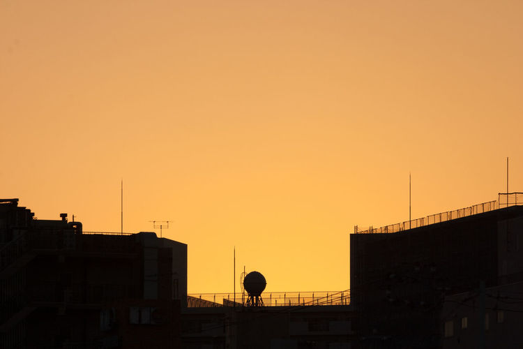Silhouette of water tower against sky during sunset