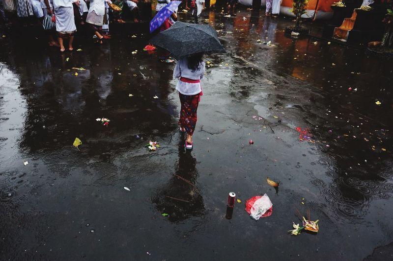 Low Section Of Man Walking On Wet Street