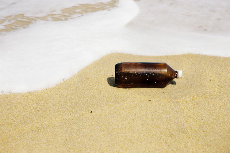 High angle view of bottle on sand at shore