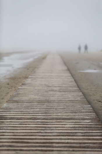 Surface level of boardwalk against clear sky