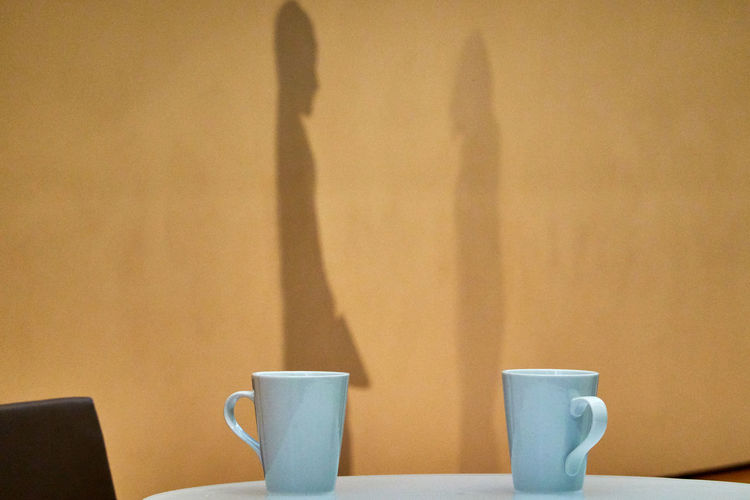 Close-up of coffee cup on table against wall and person shadows