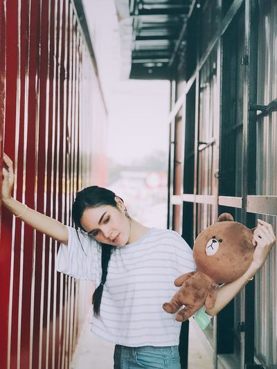 Young woman holding teddy bear while standing amidst walls