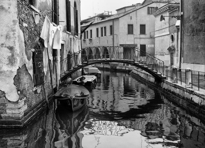 Rowboats moored on grand canal by arch bridge amidst old buildings