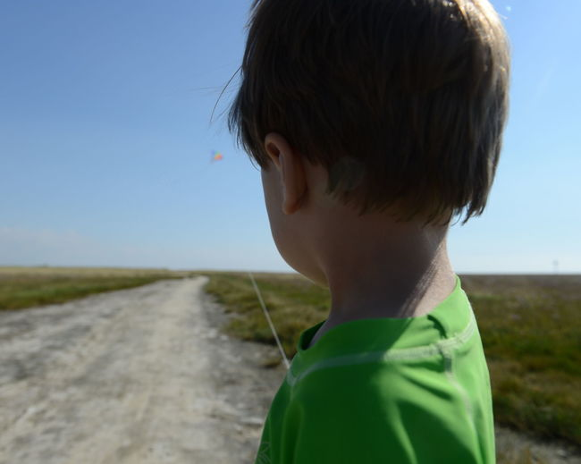Boy standing on road amidst grassy field against sky during sunny day