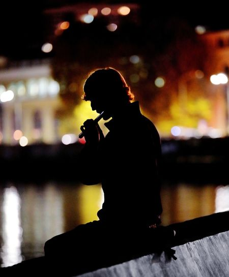 Silhouette Man Playing Flute At Night