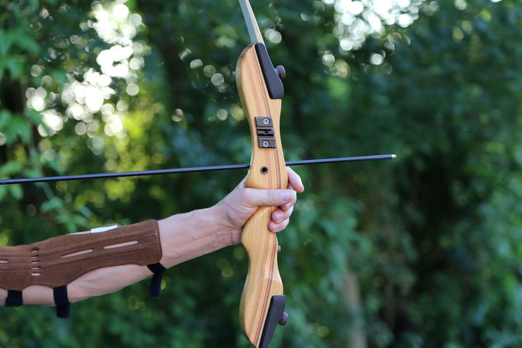 Human Hand Holding Focus On Foreground Hand One Person Day Arrow - Bow And Arrow Aiming Tree Human Body Part Archery Wood - Material Leisure Activity Weapon Sport Plant Nature Close-up Playing Finger Bow