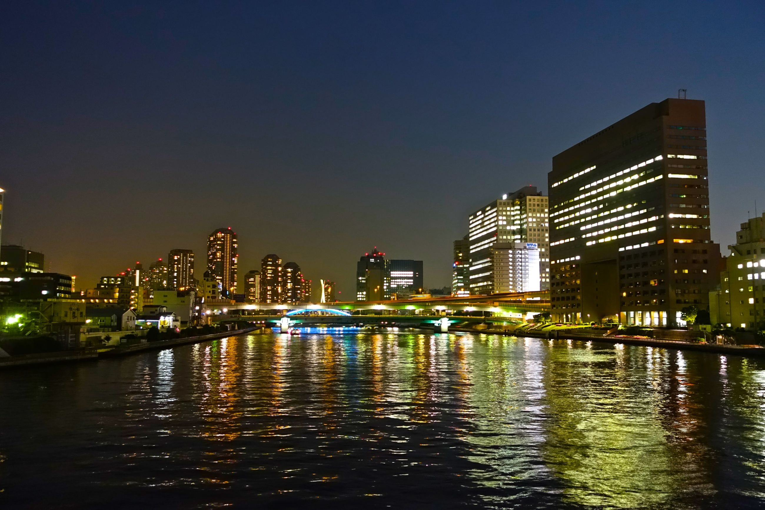 building exterior, architecture, illuminated, built structure, water, night, city, waterfront, reflection, clear sky, river, building, copy space, cityscape, skyscraper, sky, city life, modern, residential building, urban skyline