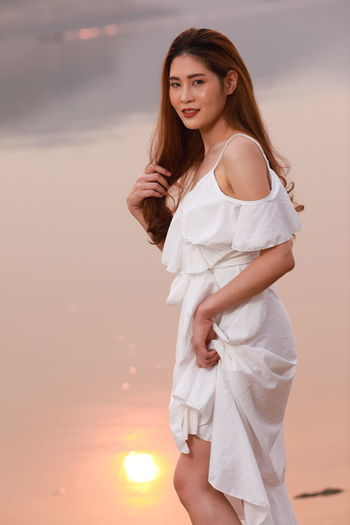 Portrait of a smiling young woman standing against sky during sunset