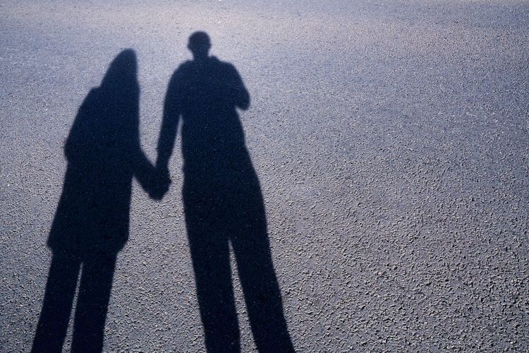 Shadow of couple holding hands on road