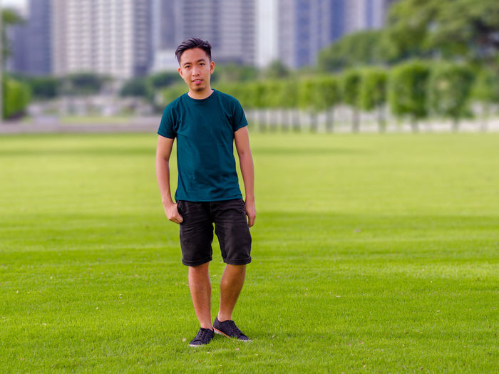 Portrait Of Young Man Standing On Grassy Field