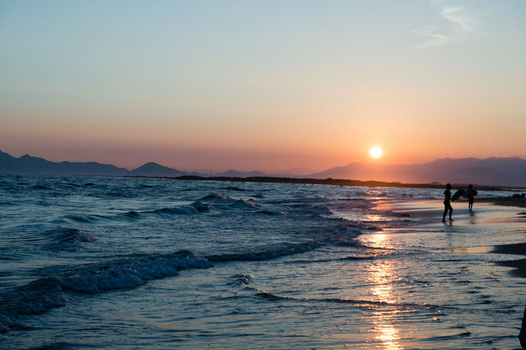 Beach Beauty In Nature Horizon Over Water Idyllic Land Leisure Activity Lifestyles Nature Orange Color Outdoors People Real People Reflection Scenics - Nature Sea Silhouette Sky Sun Sunset Water Wave