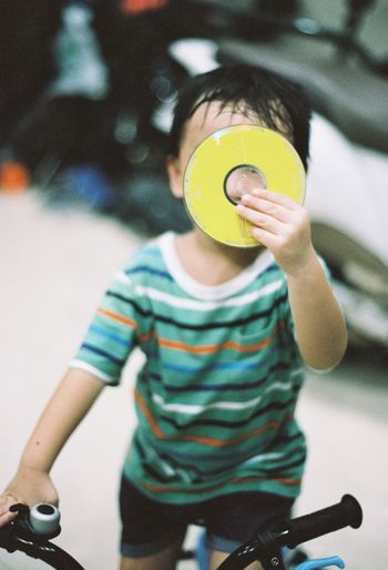 Boy holding compact disc while riding bicycle on floor