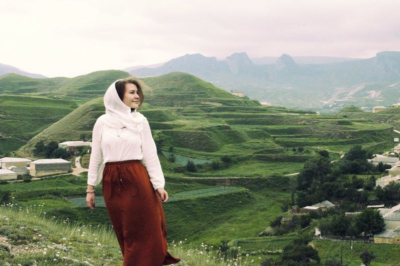 Young Woman Standing On Caucasus Mountains Against Sky