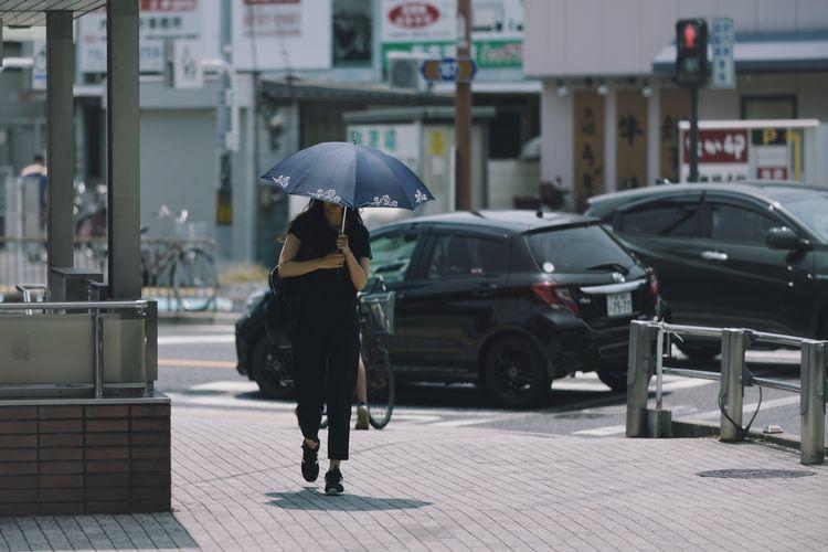 Full length of man walking on street in rainy season
