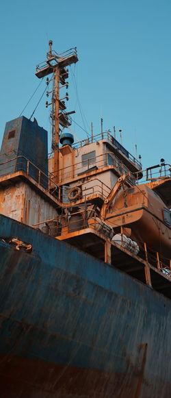 Rusty ship against clear blue sky