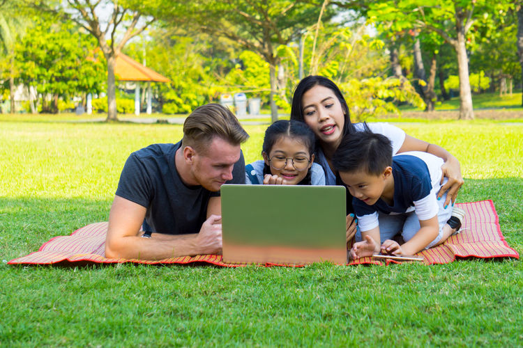 Young family with children having fun in nature park Adult Boys Child Childhood Communication Daughter Day Family Father Females Girls Grass Internet Laptop Mature Adult Men Mid Adult Mother People Sitting Son Technology Togetherness Using Laptop Wireless Technology