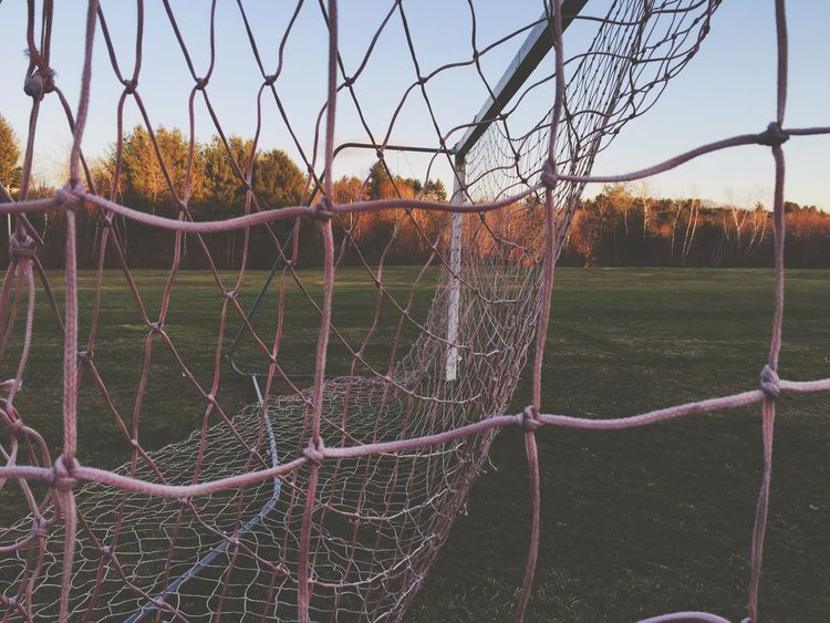 Distant Distance Peaking Grass Peaking Through Shootermag Green Field Sports Sports Equipment Net Pink Pastel Outdoors Soccer Field High School Sports Goal Trees Soccer Net Soccer