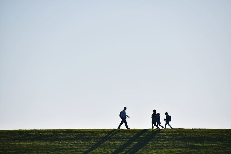 Family Walking On Field Against Clear Sky