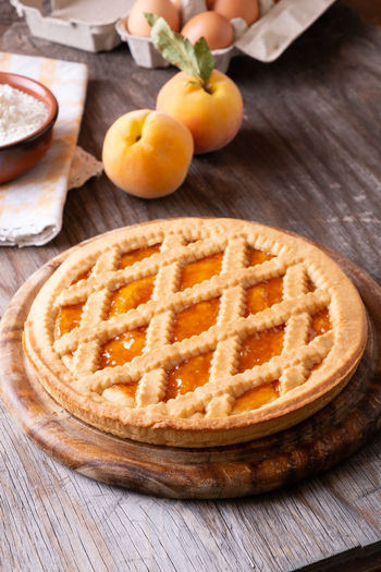 Tart with peach jam on wooden rustic table Baked Baked Pastry Item Close-up Cutting Board Dessert Dough Food Food And Drink Freshness Fruit Healthy Eating Indoors  Orange Orange Color Pastry Dough Peaches Pie SLICE Snack Sweet Sweet Food Table Tart - Dessert Temptation Wood - Material