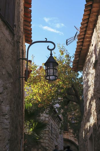 Low angle view of street light by building