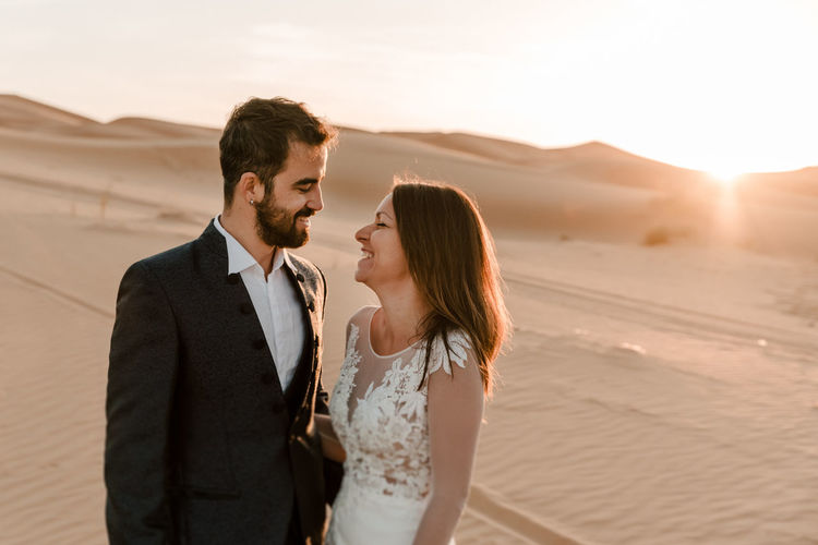 A couple in their wedding dresses in the desert are having fun while posing in the desert.
