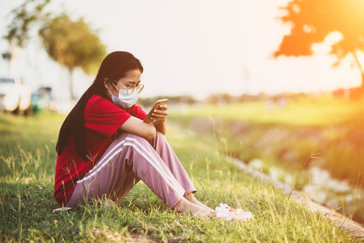 Woman using mobile phone while sitting on grass