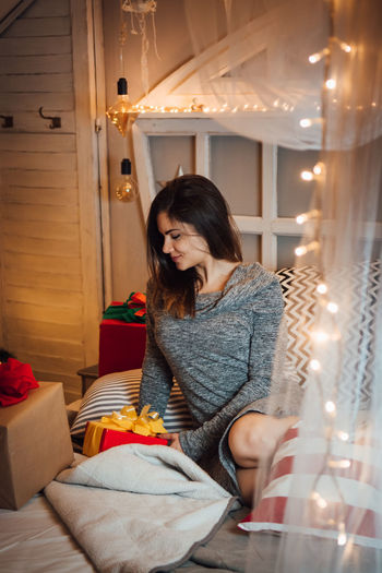 Woman looking away while sitting on illuminated lamp at home