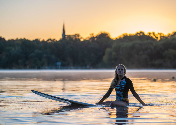 Woman sitting on surfboard at lake during sunset