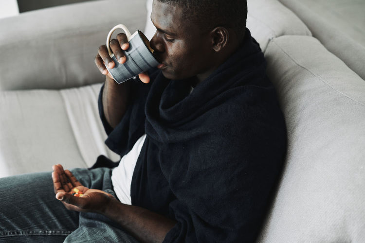Midsection of man wearing hat while sitting on sofa at home
